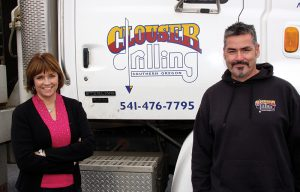Kevin and Helen Gill own Clouser Drilling and pose in front of one of their drilling rigs
