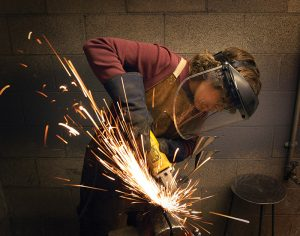student making sparks fly whil grinding metal with a safety mask on