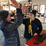 A pair of student workers at the Redwood Campus library give each other a high five.