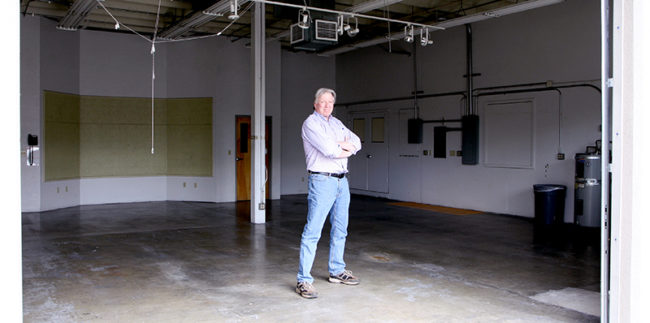 Tracy Thompson, director of the Rogue Innovation Hub, stands in an spacious room that will be transformed into a wood and metal shop.
