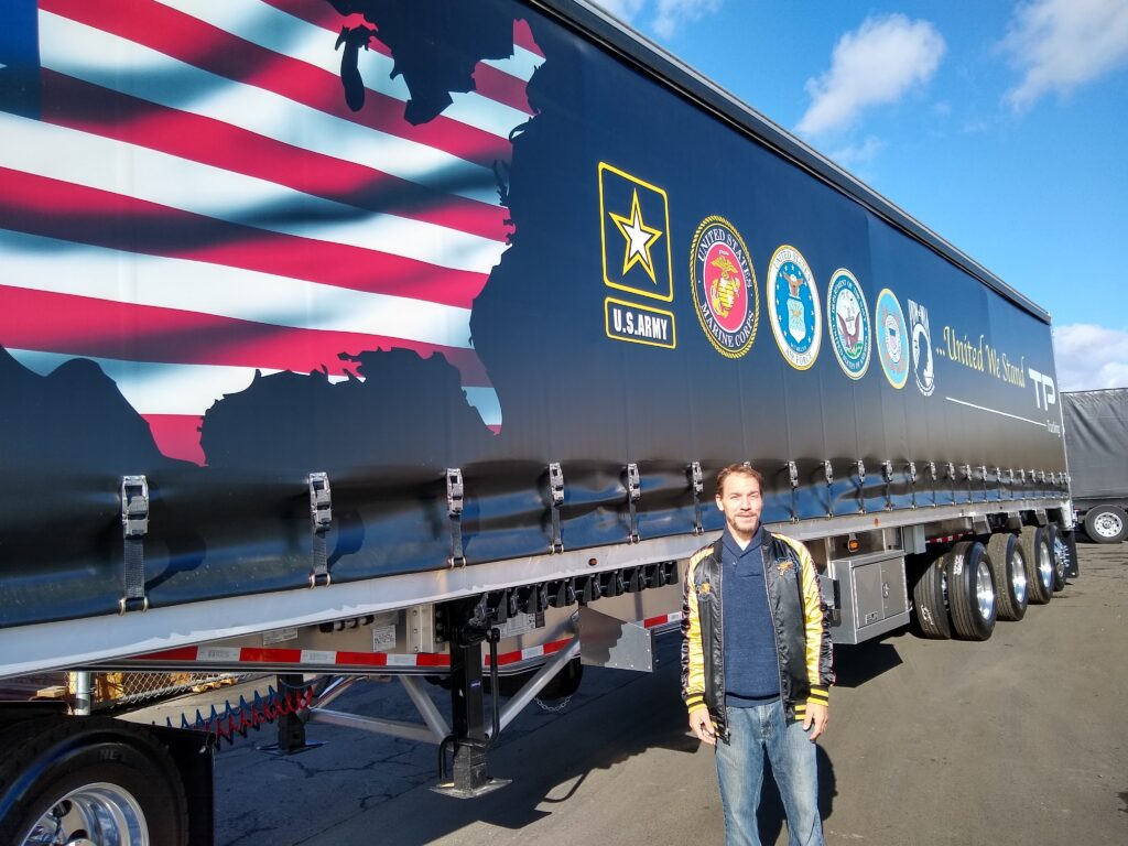 RCC Design & Digital Media student Wrenn Arbouin stands next to a TP Trucking trailer with a design he created honoring America's armed forces and veterans.